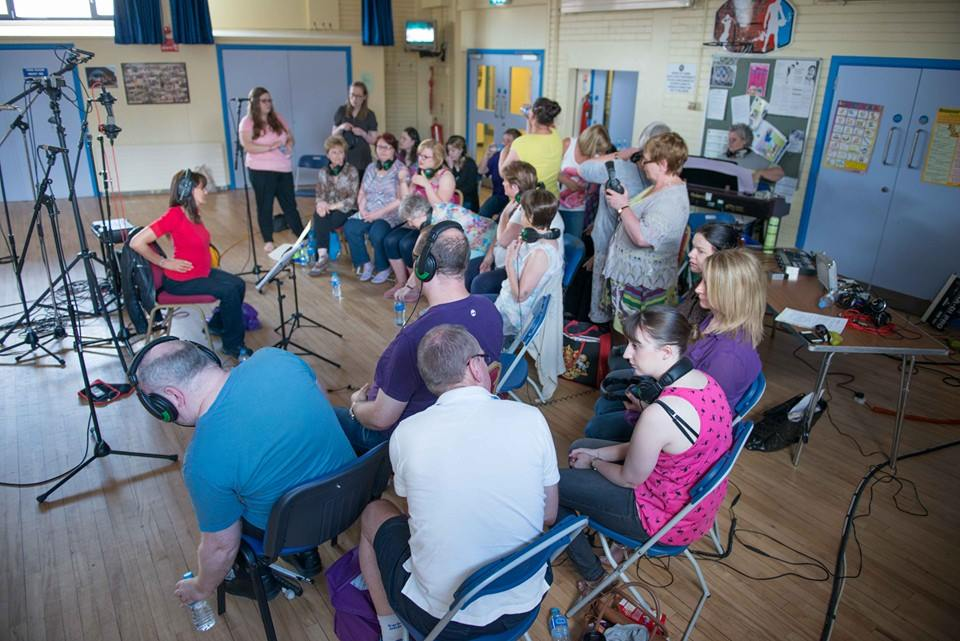 Choir are in Divis community centre wearing headphones ready to record their album 3